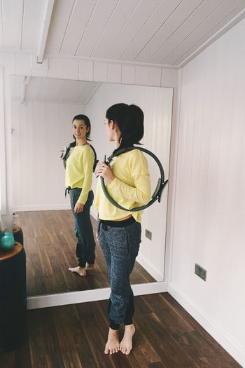 Full length of woman standing in front of a mirror in a pilates studio