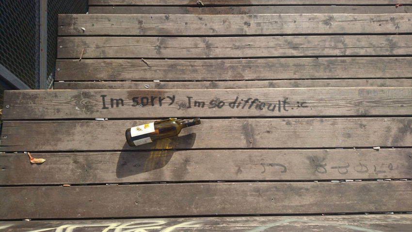 """The message """"I'm sorry I'm so difficult"""" written with a sharpie on a public wooden structure, an empty wine bottle next to it. Emotions Guilt Relationship Sorry Text Wine Bottle Wood Apologize Apology Close-up Communication Day Empty Wine Bottles Expression Forgive Message Mistake No People Note Outdoors Regret Remorse Words"""