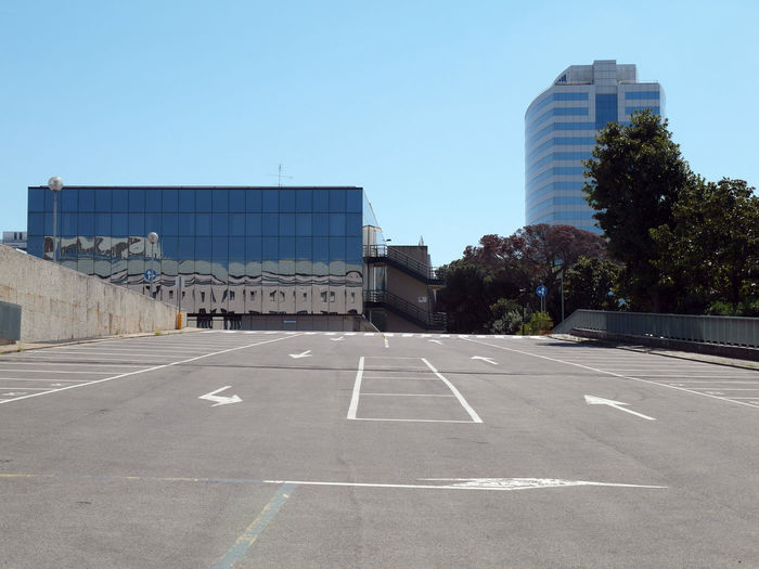 Empty road by buildings against clear blue sky