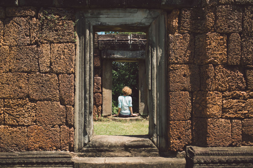 Siem Reap Cambodia Angkor Girl Curly Hair Architecture Real People One Person Built Structure Day Rear View Women Lifestyles Building History Childhood Leisure Activity Sitting Adult The Past Casual Clothing Outdoors Full Length Females Architectural Column