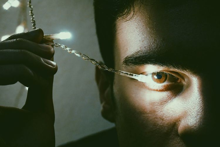 Cropped Eye Of Man With Illuminated String Light In Darkroom