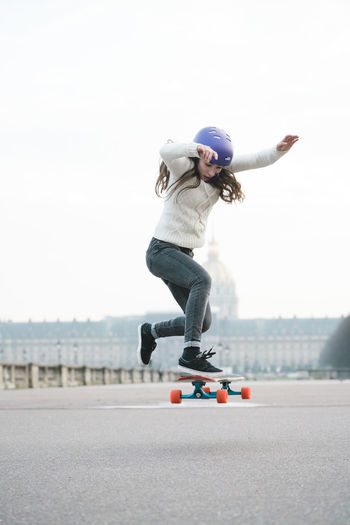 Full length of man skateboarding in city against sky