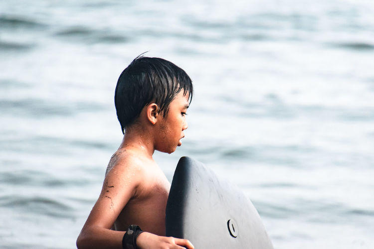 Shirtless boy with surfboard on beach