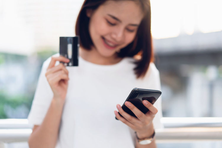 Woman holding credit card pay online and using smartphone for shop through the website. Concepts online shopping for convenience. Wireless Technology Mobile Phone Holding Technology Communication Smart Phone Portable Information Device Telephone One Person Using Phone Young Adult Text Messaging Connection Front View Adult Young Women Smiling Focus On Foreground Women Outdoors Beautiful Woman Hairstyle