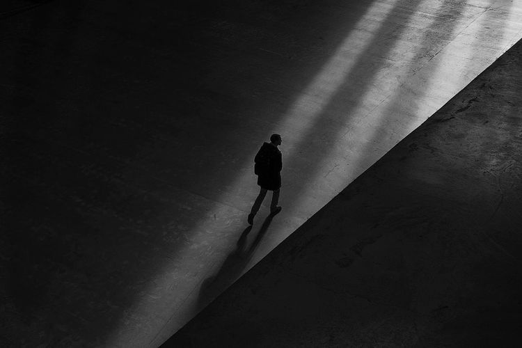 High angle view of silhouette man walking on umbrella