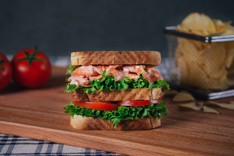 Sandwich Bread Burger Close-up Cutting Board Day Focus On Foreground Food Food And Drink Freshness Healthy Eating Indoors  Lettuce Meat Minced No People Ready-to-eat Salmon Salmon Sandwich Sandwich Table Tomato Vegetable Wood - Material