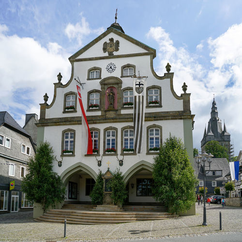 Brilon, North Rhine Westphalia / Germany - June 23th 2018: Brilon city hall decorated with flags. It is celebrated shooting match. On the right the Propsteikirche Brilon North Rhine Westphalia Town Hall Historic Building Old Town Downtown Market Square Church Propstei Church Tourism Festival Rifle Festival Shooting Match Flags Blue Sky Summer Trees Administration City City Administration Stairway Cobblestone Architecture Unknown People Bollard Lantern Sauerland Window Lattice Window Gable Rifle Club Comission Authority Guildhall Old Planter Staircase Slate Bow Antler Shrine Birch Pennant Building Exterior Sky Cloud - Sky Façade Low Angle View Clock