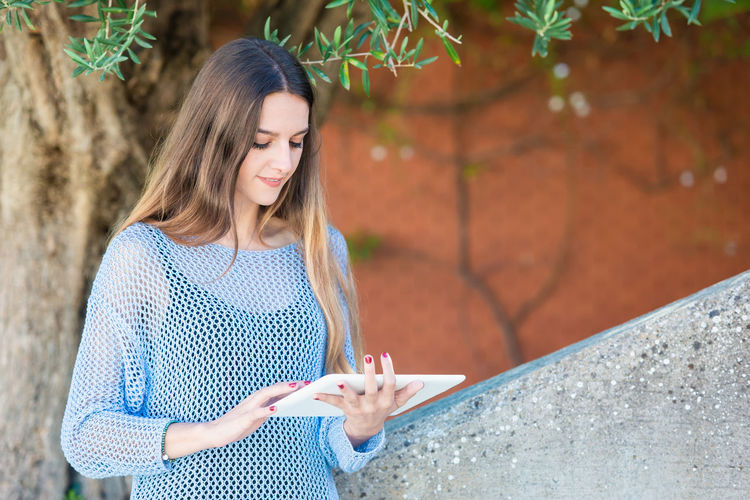 Smiling woman using digital tablet against tree