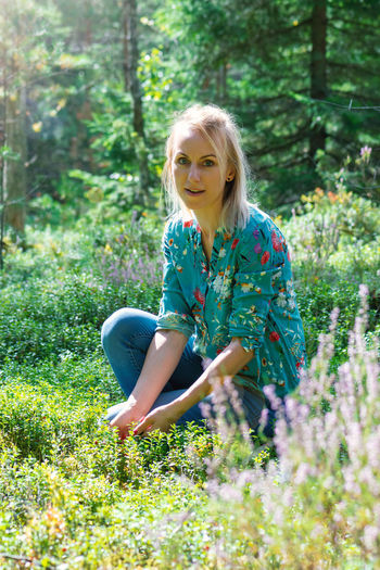 Portrait of woman sitting amidst plants in forest