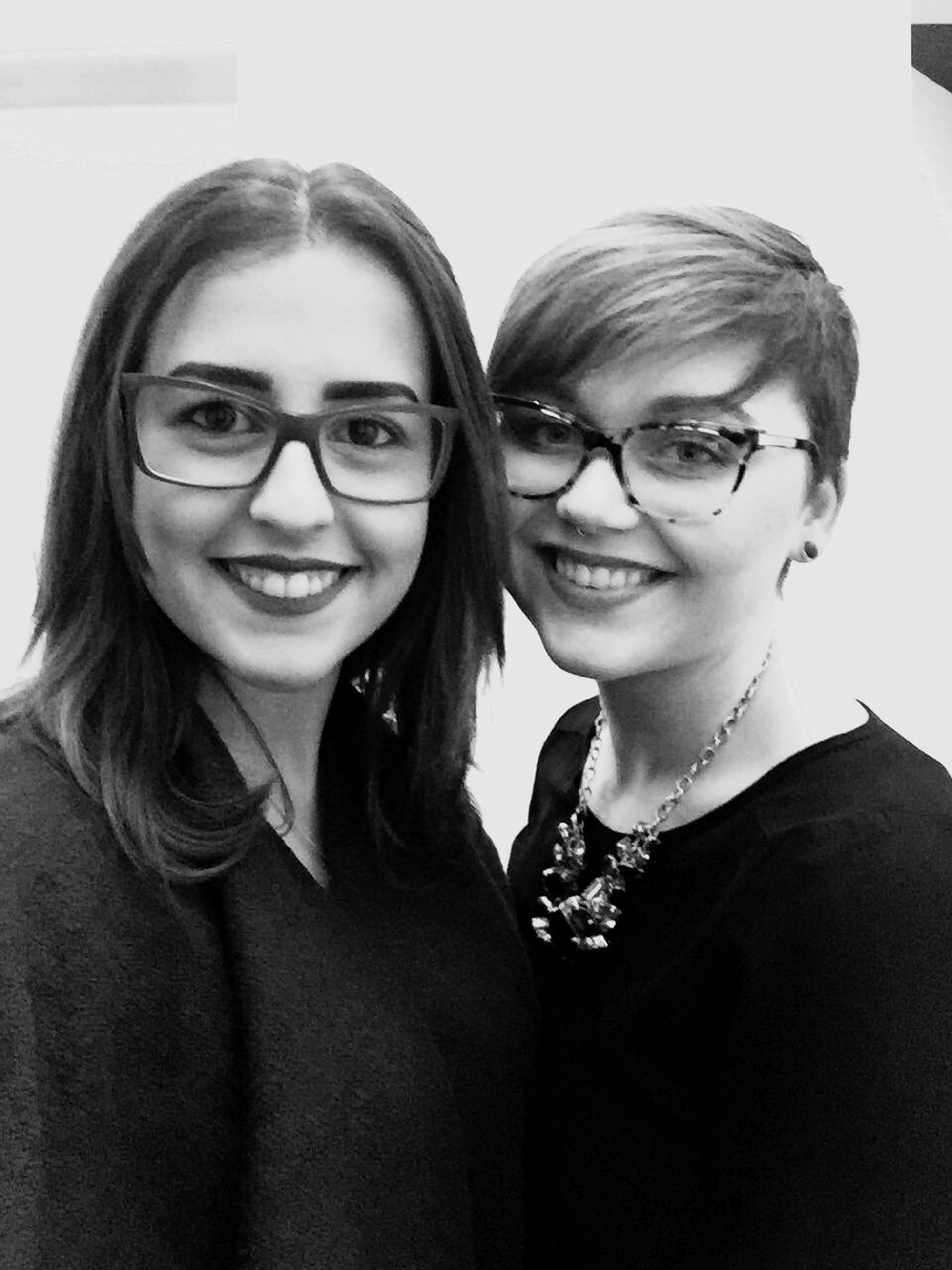 two people, eyeglasses, real people, smiling, looking at camera, portrait, lifestyles, young women, glasses, leisure activity, happiness, close-up, togetherness, young adult, indoors, cheerful, day