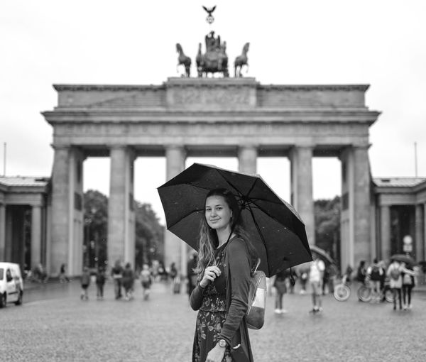 Portrait of smiling woman holding umbrella in front of historical building