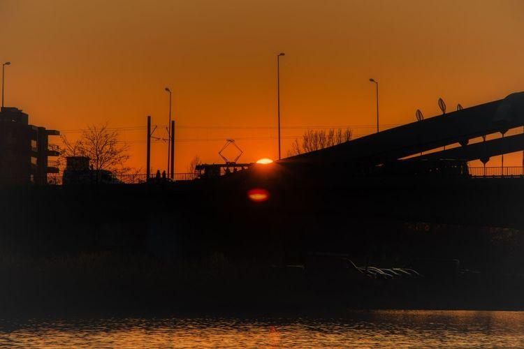 Silhouette bridge over river against orange sky