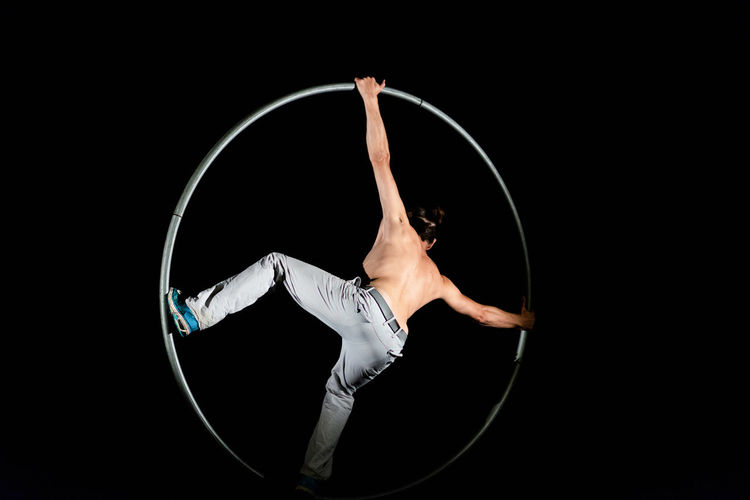 Circus Acrobat Agility Arms Raised Balance Black Background Circle Dancing Elégance Flexibility Full Length Geometric Shape Healthy Lifestyle Human Arm Indoors  One Person Performance Plastic Hoop Skill  Sport Studio Shot Young Adult
