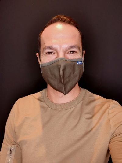 Portrait of man wearing mask against black background