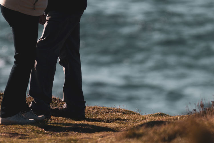 Low section of couple standing on beach