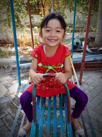 Looking At Camera Portrait Real People Childhood Front View Smiling Black Hair Elementary Age One Person Happiness Red Sitting Tree Day Outdoors People Asian Children Fashion Stories