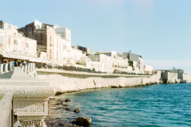 Close-up of buildings by sea against clear sky