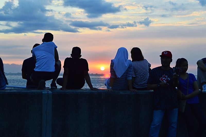 Rear view of people sitting against sky during sunset