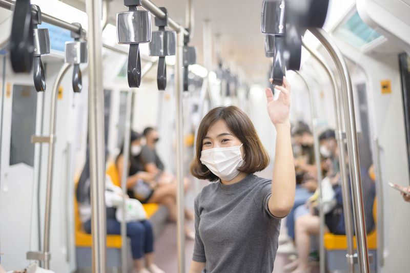 Portrait of young woman wearing mask standing in train