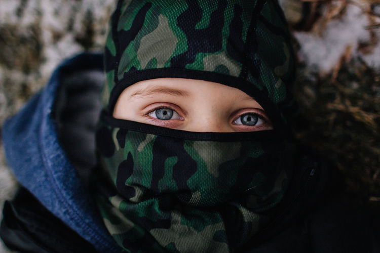 Portrait Looking At Camera One Person Headshot Child Close-up Green Color Front View Childhood Innocence Military Warm Clothing Human Face Blue Eyes Winter Ski Mask