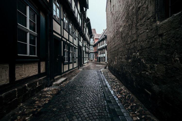 Footpath amidst buildings in city