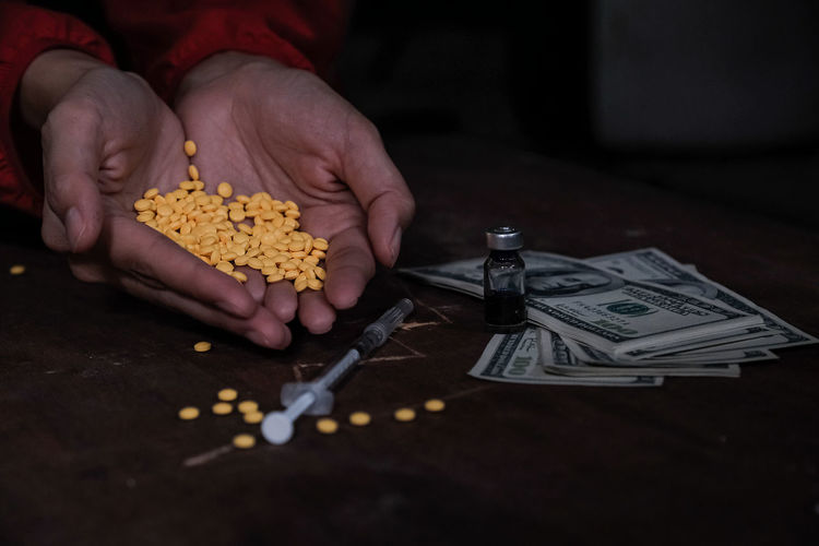 Close-up of hand holding pills with drug and paper currency on table
