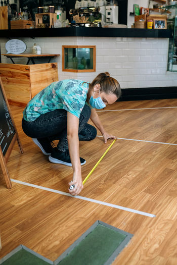 Full length of woman measuring floor