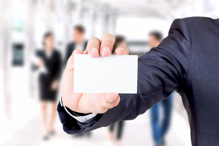 Businessman holding white business card isolated on white background Adult Blank Business Business Person Businessman Businesswoman Communication Corporate Business Focus On Foreground Formalwear Hand Holding Human Body Part Human Hand Incidental People Males  Men Message People Standing Suit Well-dressed
