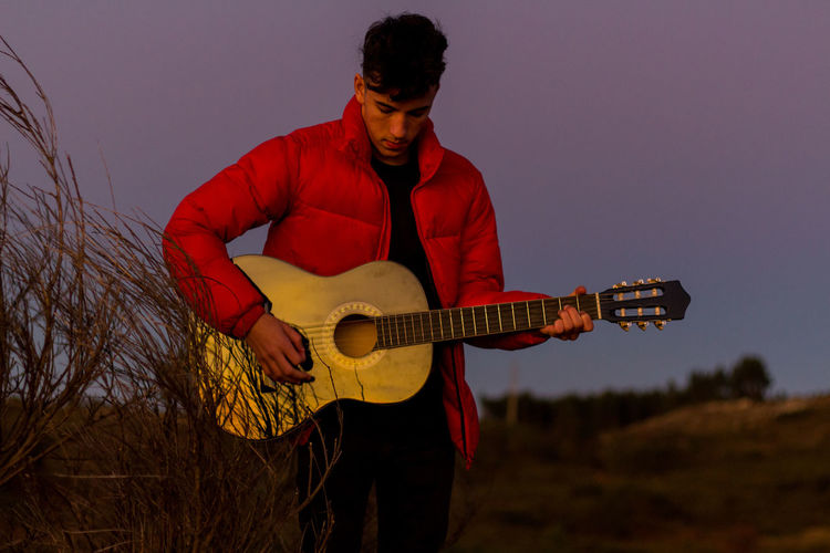 Young man playing guitar against sky at dusk