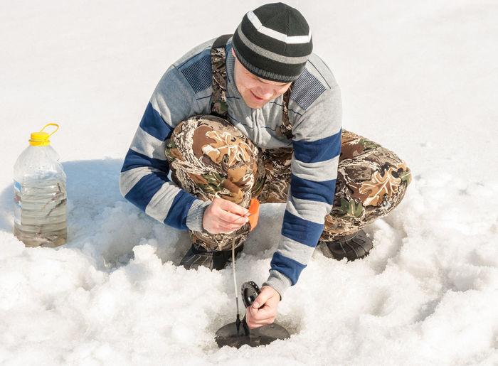 Mid adult man subglacial fishing in frozen lake