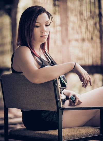 Thoughtful woman sitting on chair at home