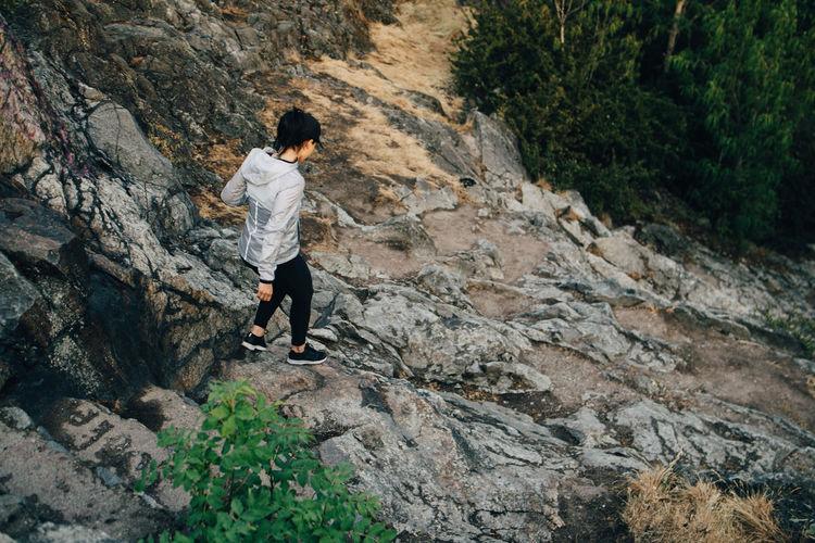 Full length rear view of man walking on rock