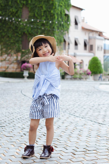 Architecture Arms Raised Child Childhood City Clothing Day Fashion Females Focus On Foreground Front View Full Length Girls Hat Human Arm Innocence Looking At Camera One Person Portrait Real People Smiling Women
