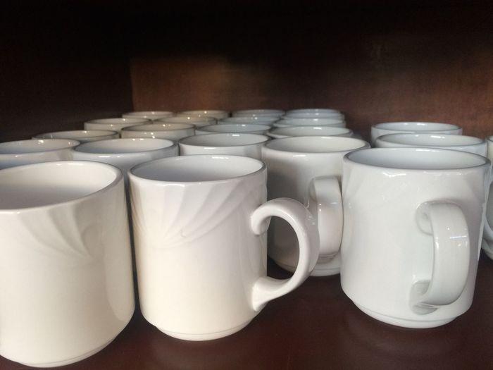 Close-up of mugs on shelf