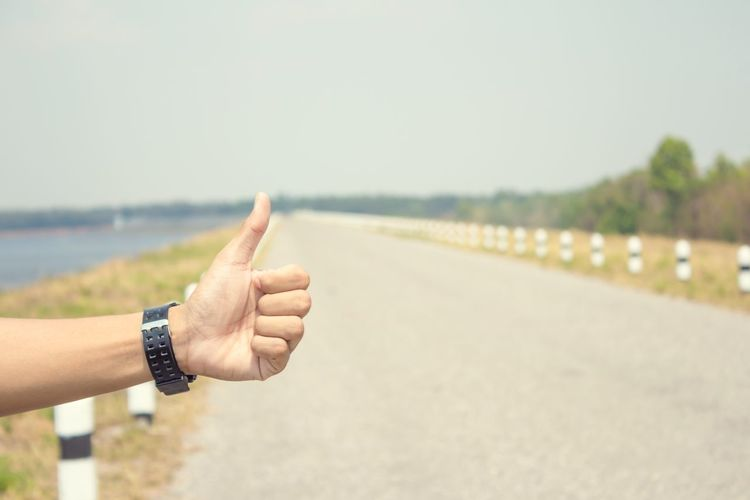Cropped hand of person gesturing while hitchhiking on road against sky