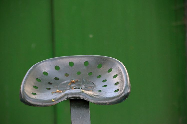 Close-up of metallic seat against green wall