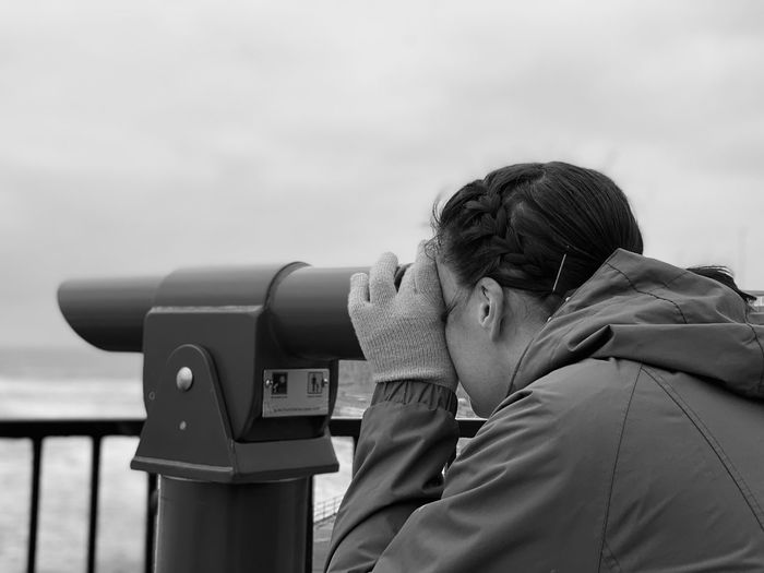 Rear view of a woman using a telescope against sky