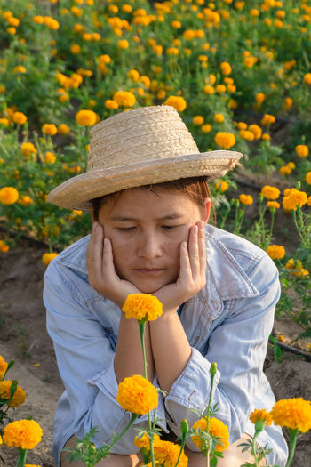 Marigold Portrait Flower Marigold Flower Farmer Selective Focus Lifestyles Outdoors Nature Plant Leisure Activity Care Check Hat Front View Flowering Plant One Person Freshness Childhood Child Holding Growth Day Clothing Casual Clothing Sun Hat Gardening Pre-adolescent Child Innocence