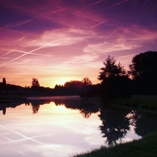 Vapour trails at dawn reflected in the fishing ponds at Soissons-Compiegne, France. Tranquility Cloud - Sky Dawn Lake Reflection Reflections In The Water Sunrise Sunrise_sunsets_aroundworld Tranquil Scene Tranquility Vapour Trails Water