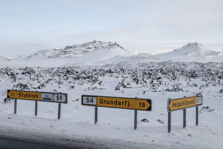 Information sign on snow covered mountain against sky