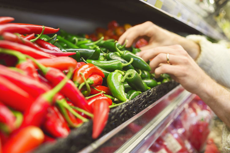 Midsection of man with red chili peppers in market