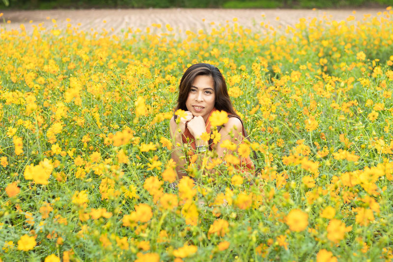 Beauty In Nature Field Flower Flowering Plant Fragility Freshness Front View Growth Hair Hairstyle Land Leisure Activity Lifestyles Long Hair Nature One Person Outdoors Plant Portrait Real People Springtime Yellow Young Adult