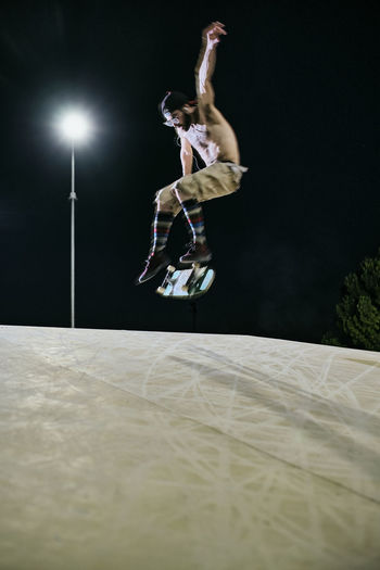 Full length of man jumping against black background