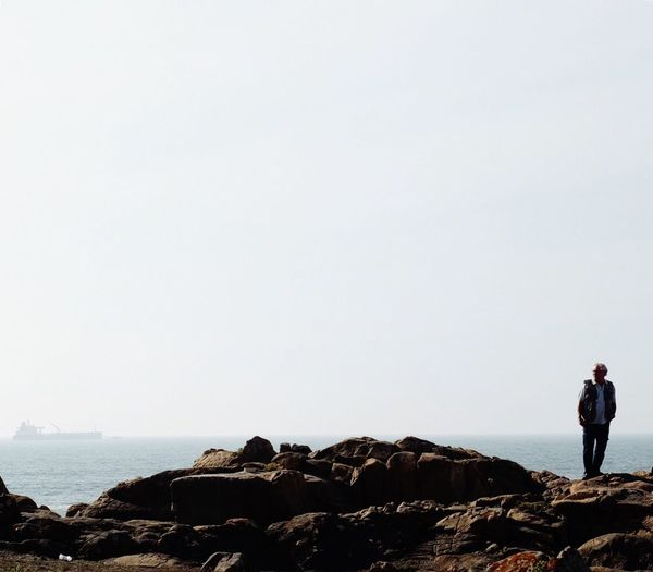 People standing on cliff by sea against clear sky
