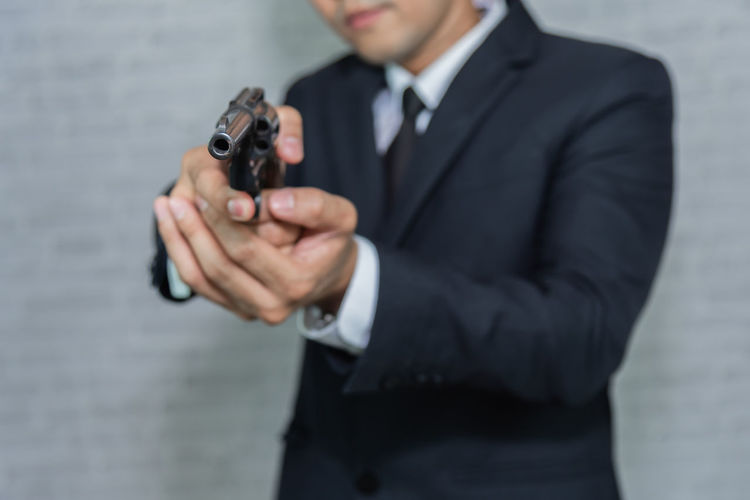 Midsection of businessman aiming with handgun