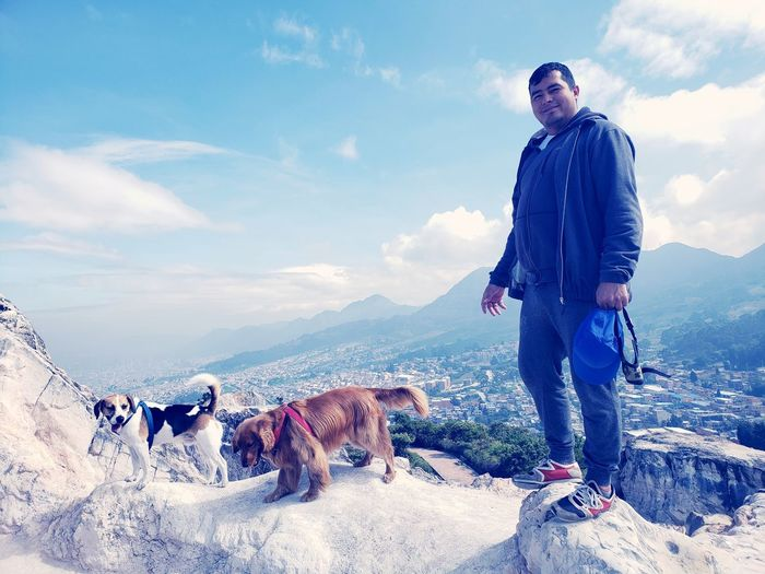 Full length of man with dogs on mountain peak against sky