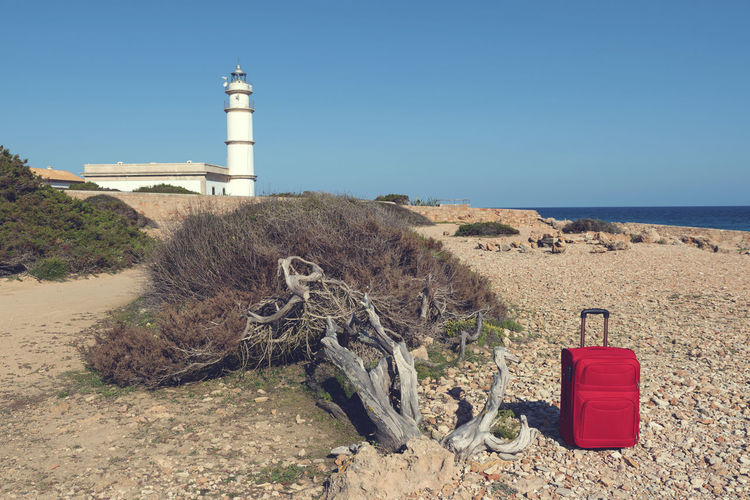 Lighthouse and red suitcase on a rocky shore at Cap de Ses Salines. Selective focus Holiday Majorca Mediterranean  Red Rocky Coastline Soft Travel Trip Vacations Adventure Destination Direction Journey Leisure Activity Lighthouse Luggage No People One Packing Sea Shore Suitcase Summer Tourism Water