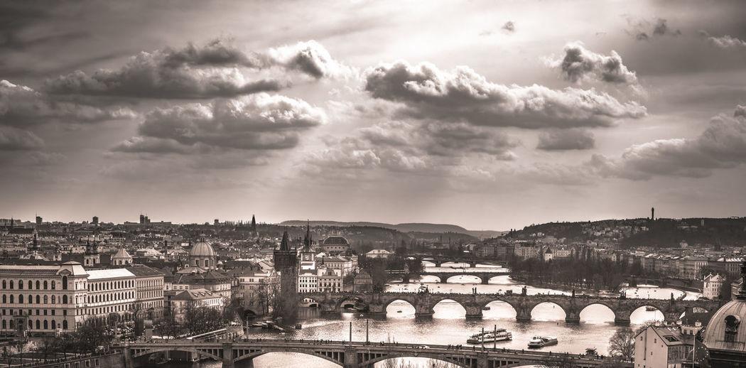 Charles bridge over vltava river against sky in city