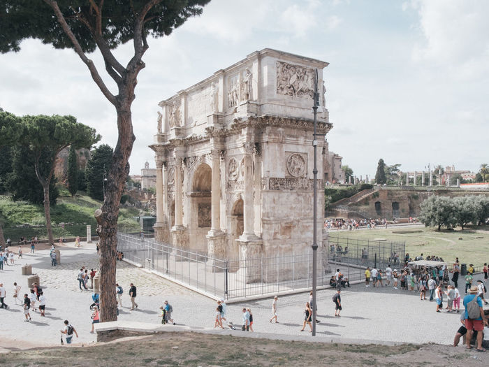 People at arch of constantine against sky
