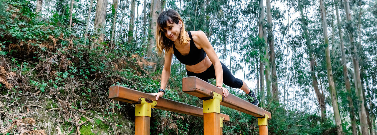 Woman exercising on parallel bars against trees